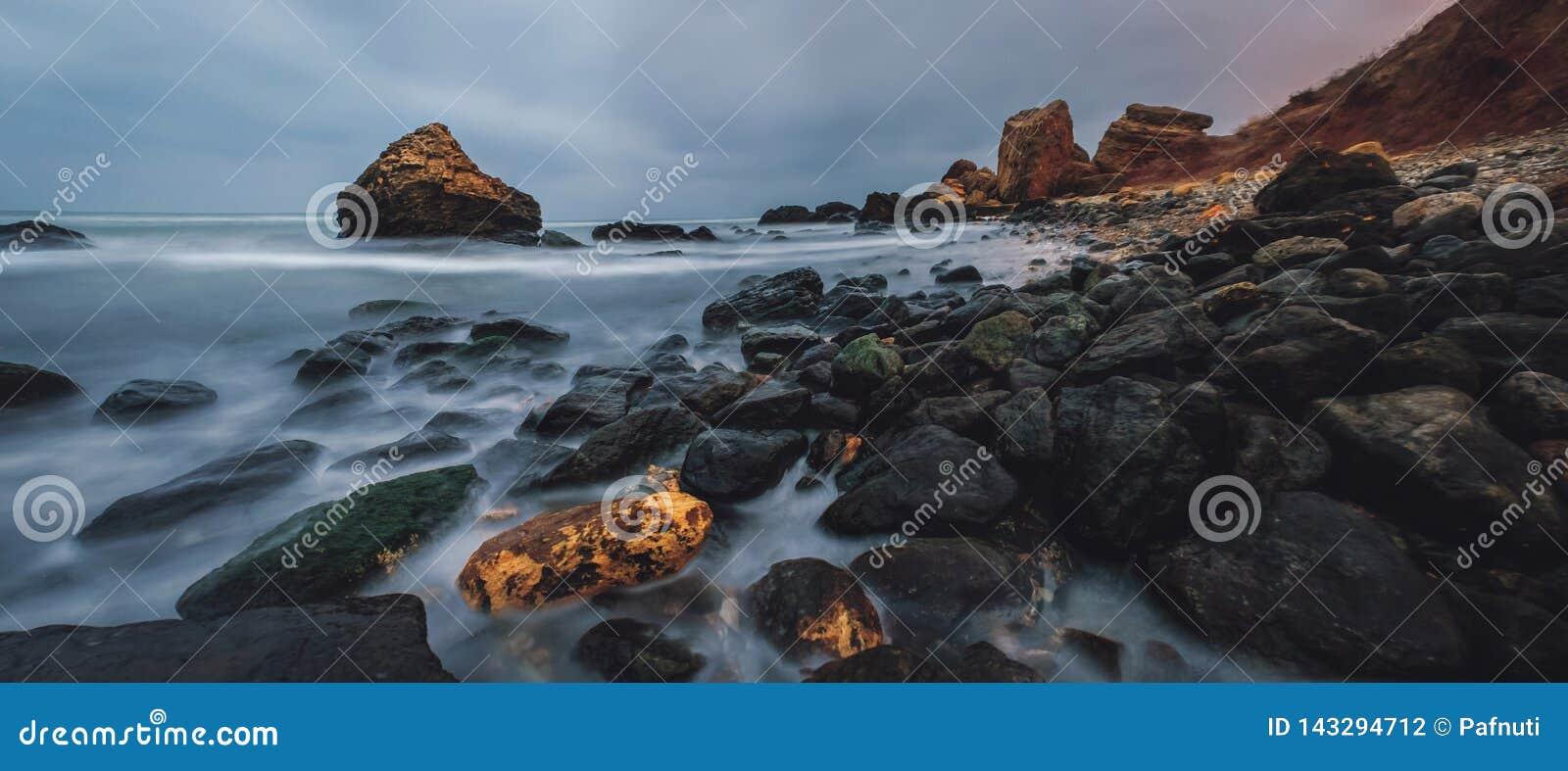 在黄昏的多岩石的海滩风景 傲德萨海滩在冬天