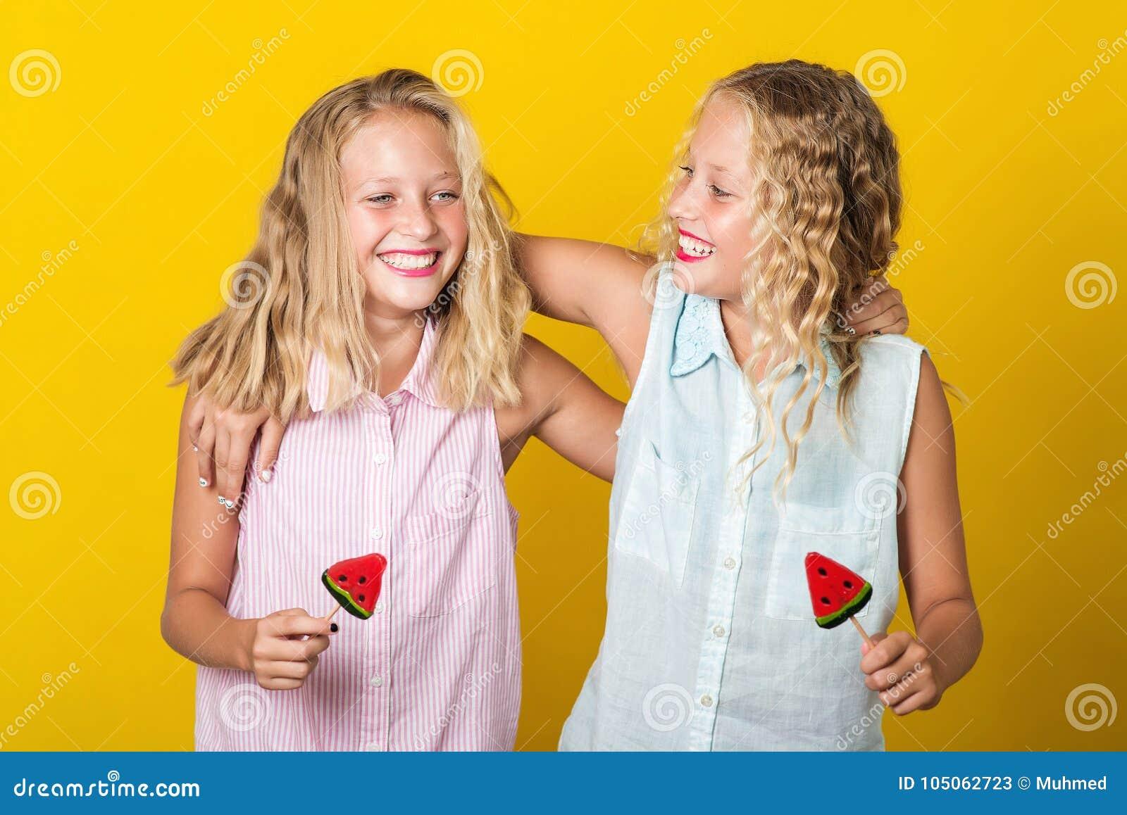在黄色背景一起孪生女孩与获得五颜六色的糖果乐趣,隔绝