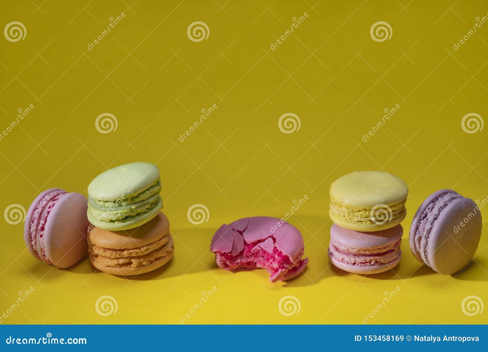 在黄色背景特写镜头的多彩多姿的通心面曲奇饼 被咬住的一 E
