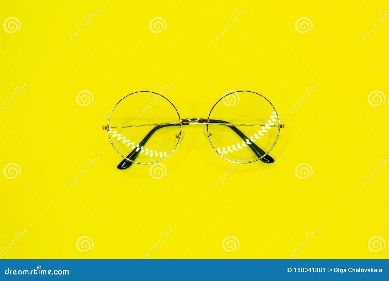 在黄色背景的圆的玻璃 一个清晰视界的时装配件