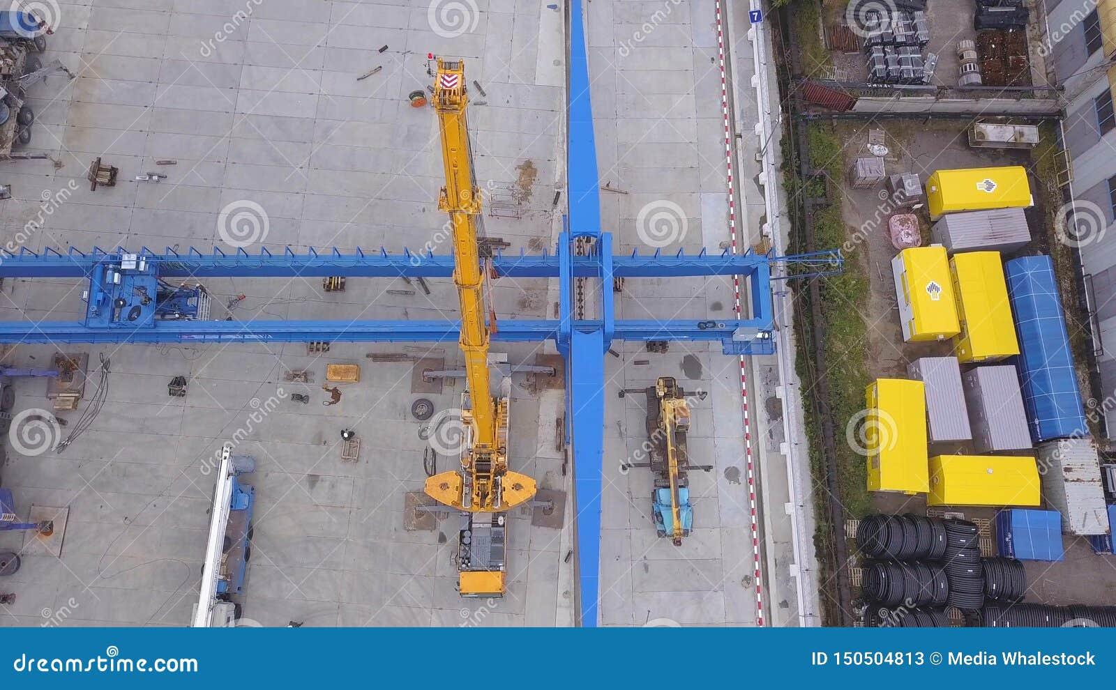 在黄色货箱附近被安装的红色和黄色建筑用起重机和铁路鸟瞰图在