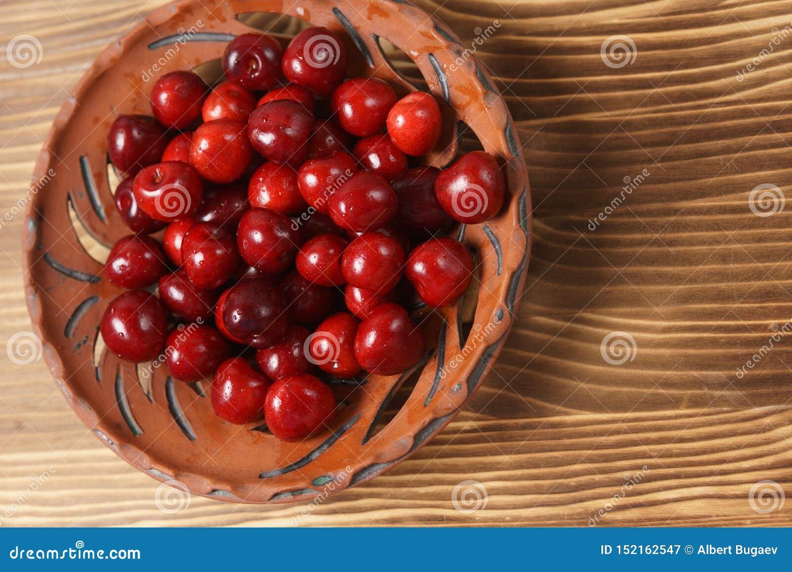 在黏土板材的红色甜樱桃在一张木桌上