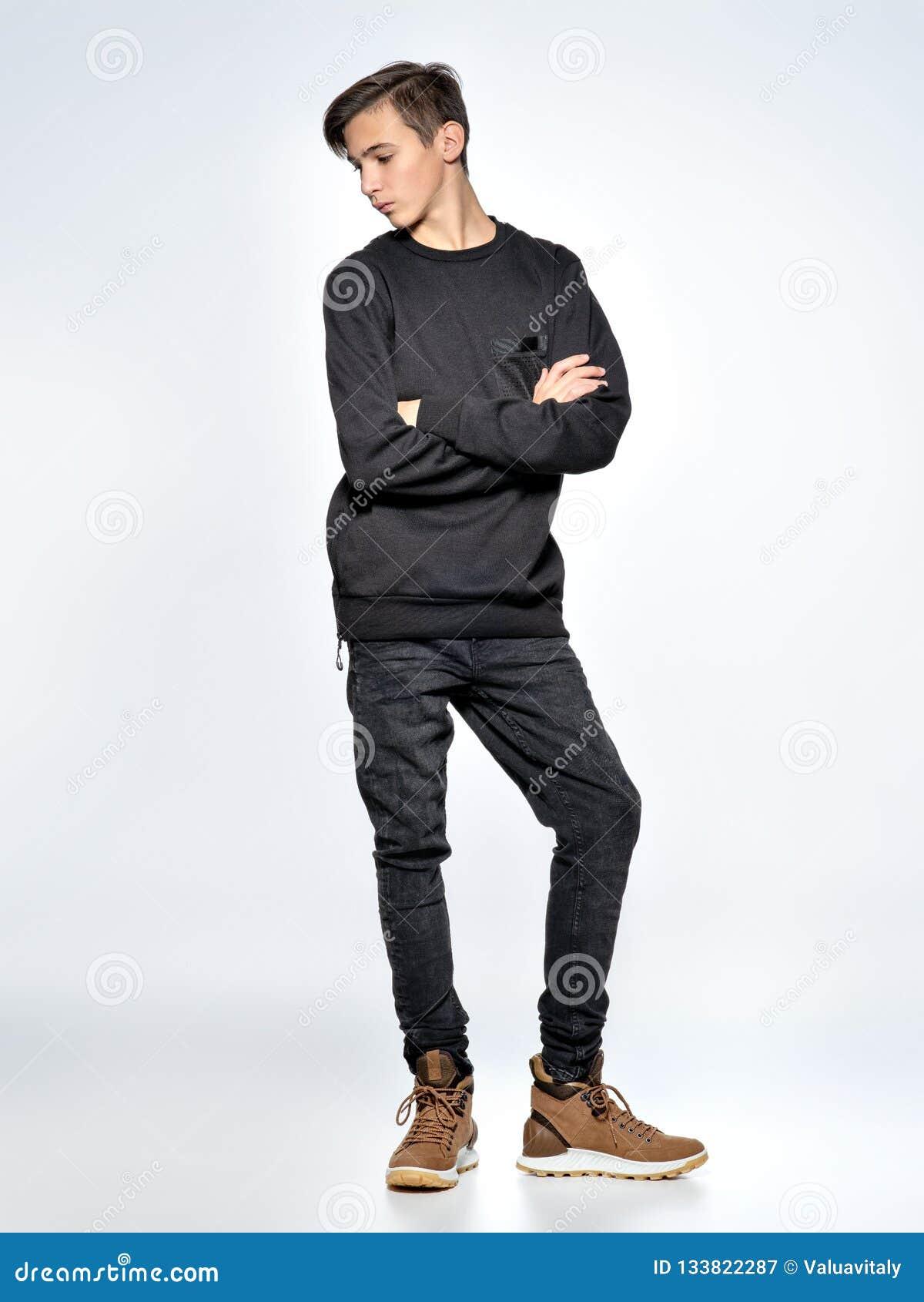 在黑时髦衣裳打扮的十几岁的男孩摆在演播室