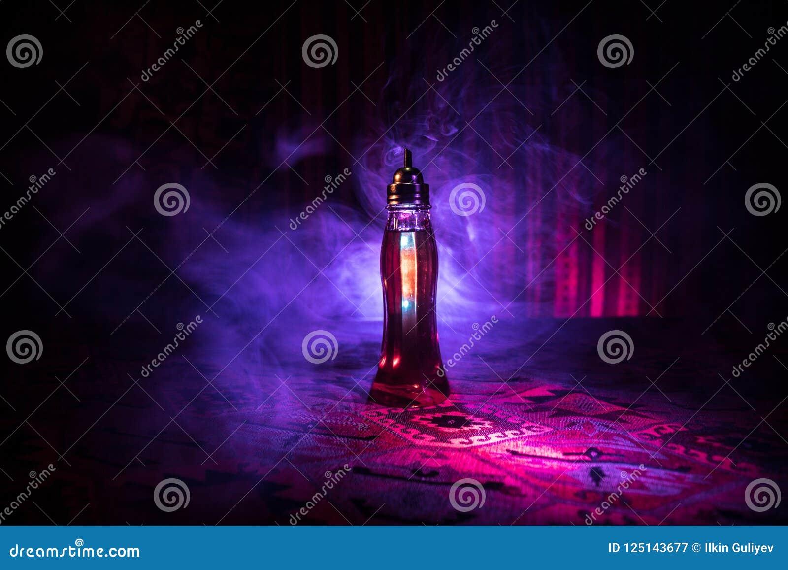 在黑暗的有雾的背景的古董和葡萄酒玻璃瓶与光 毒物或魔术液体概念