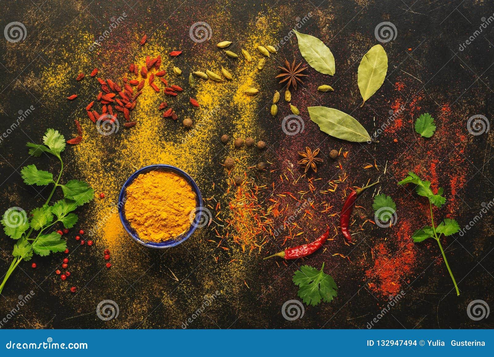 在黑暗的背景的香料,姜黄,番红花,豆蔻果实,辣椒,辣椒粉,香菜,月桂叶 各种各样色的香料