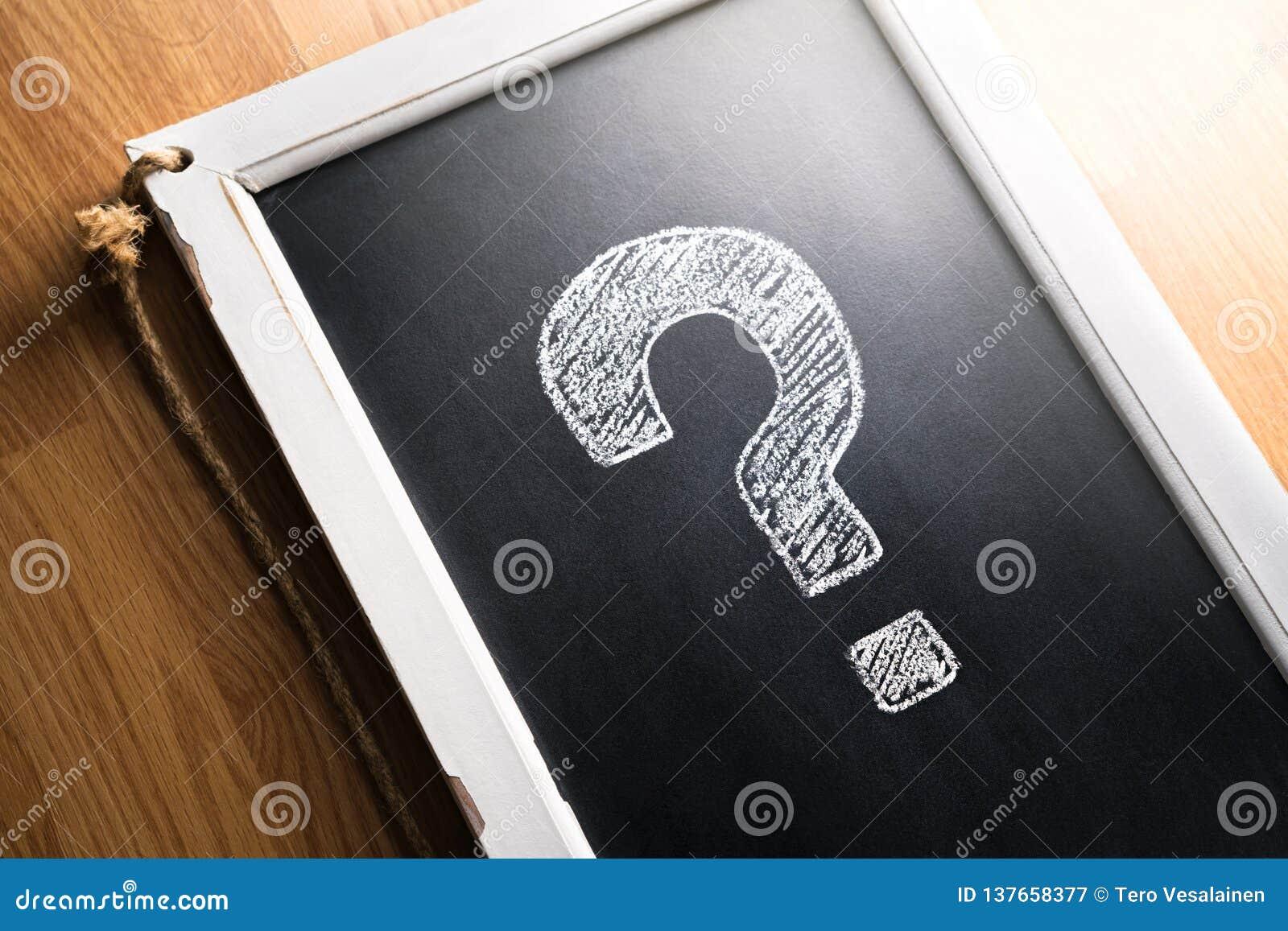 在黑板得出的问号 关于我们,帮助或者信息事务的 勘测、民意测验或者测验概念 标点,决定