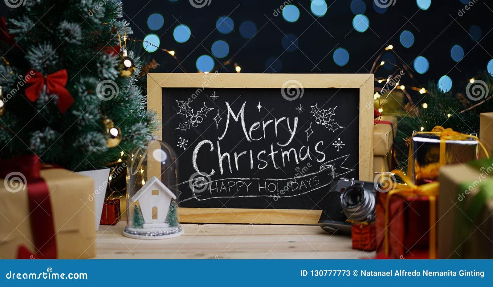 在黑板的圣诞快乐印刷术在圣诞节装饰之间