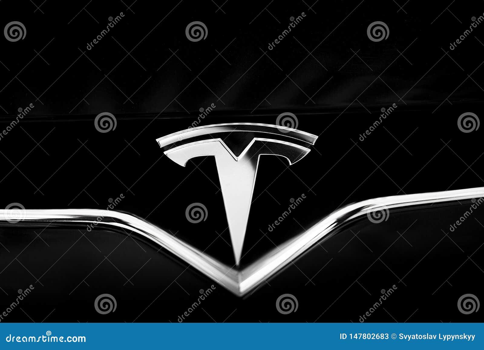 在黑汽车的特斯拉象征 特写镜头银色商标