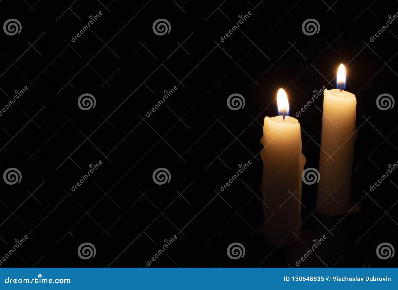 在黑背景的两个蜡烛 在黑暗中点燃蜡烛 与温暖的火焰的黄色蜡蜡烛 在memoriam横幅