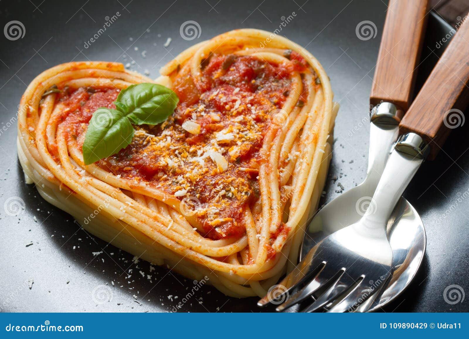 在黑背景的意粉面团心脏爱意大利食物的饮食摘要概念