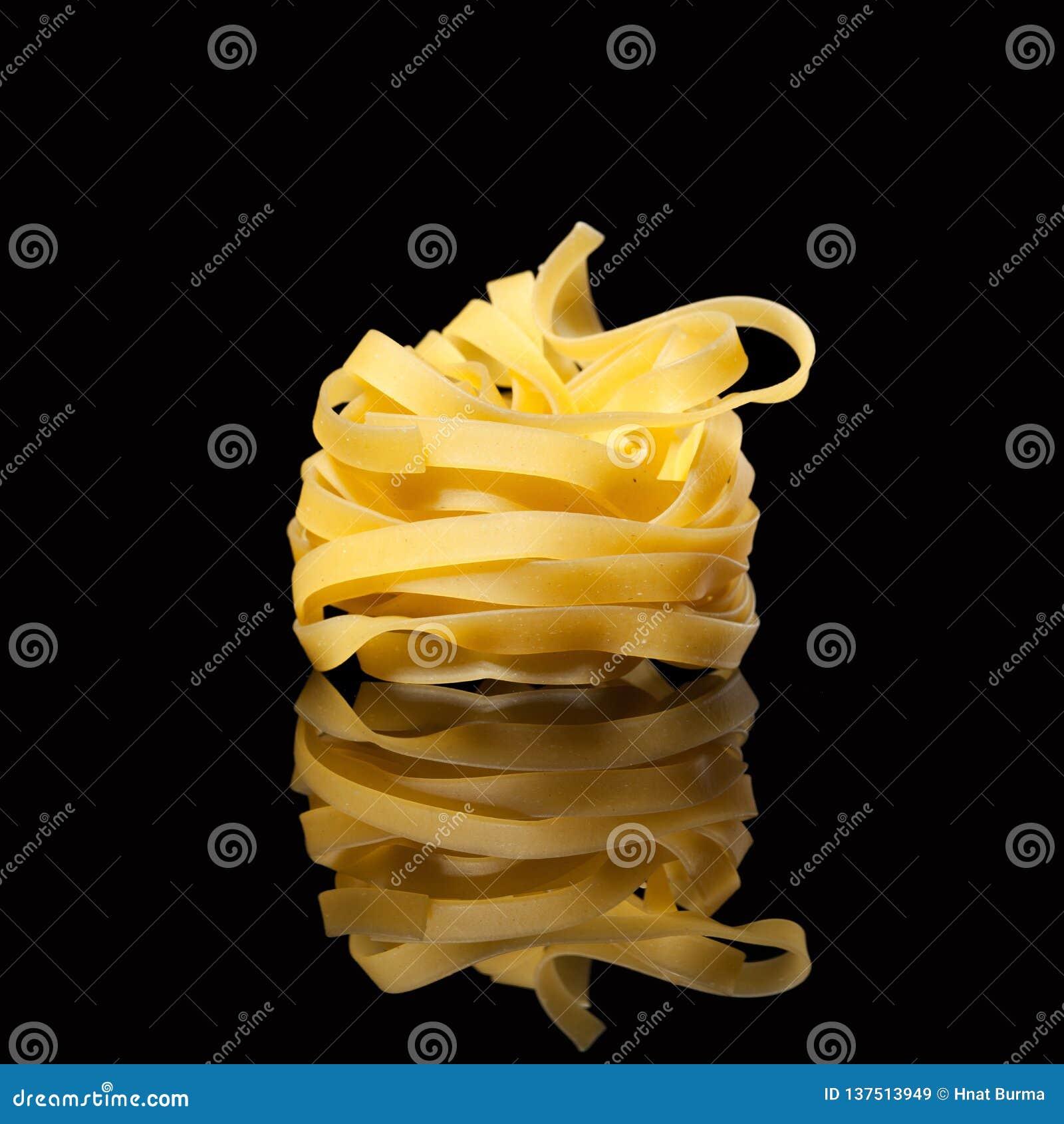 在黑背景的未加工的未煮过的tagliatelle巢与反射 传统意大利的意大利面食