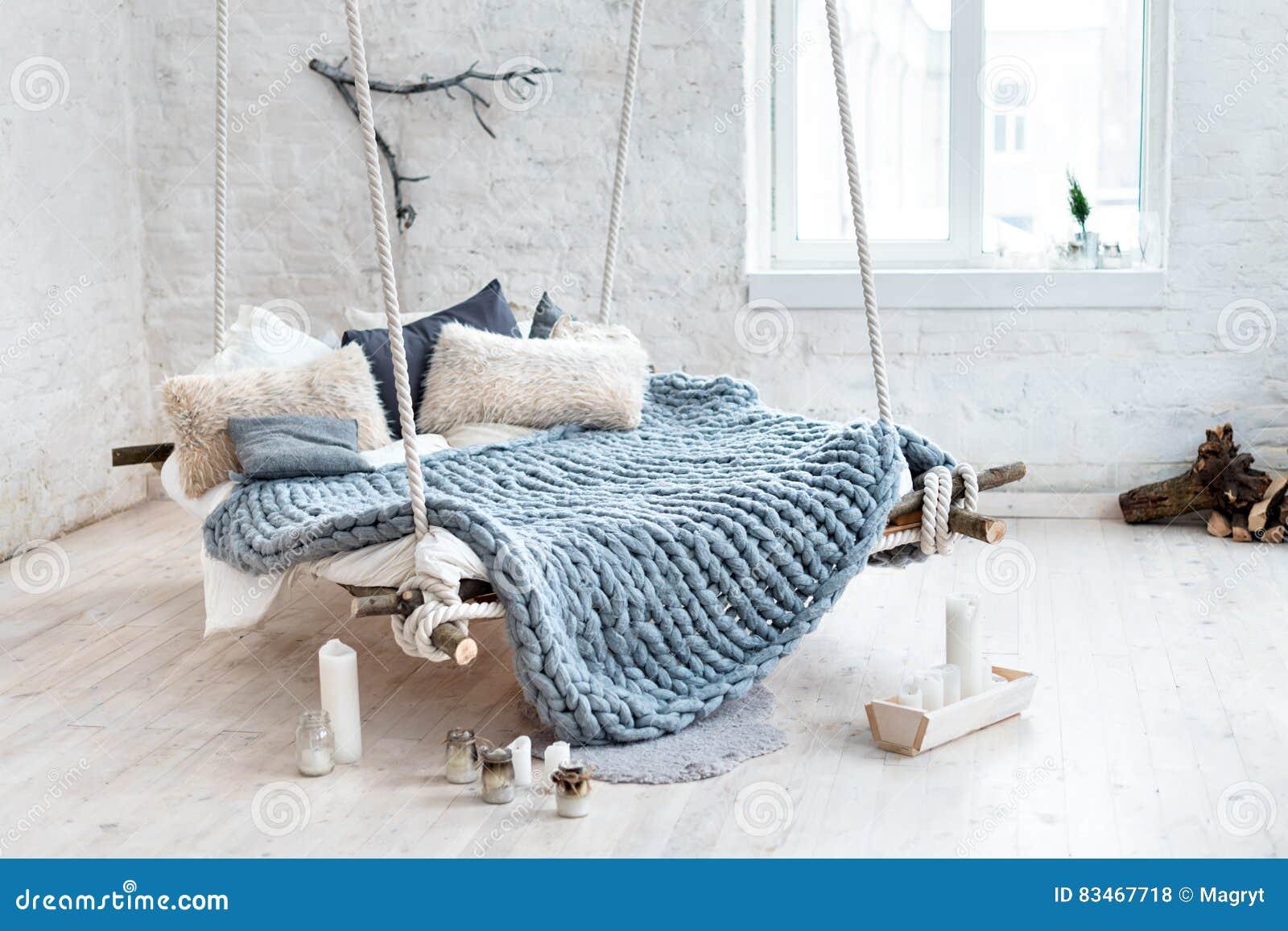 在经典斯堪的纳维亚样式的白色顶楼内部 从天花板暂停的垂悬的床 舒适大被折叠的灰色格子花呢披肩