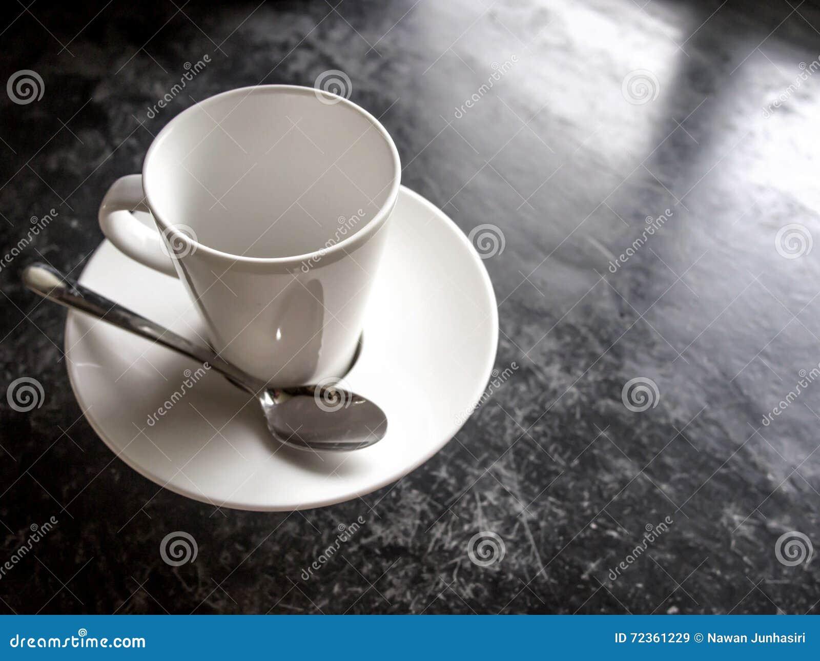 在黑地板上的空的白色杯子