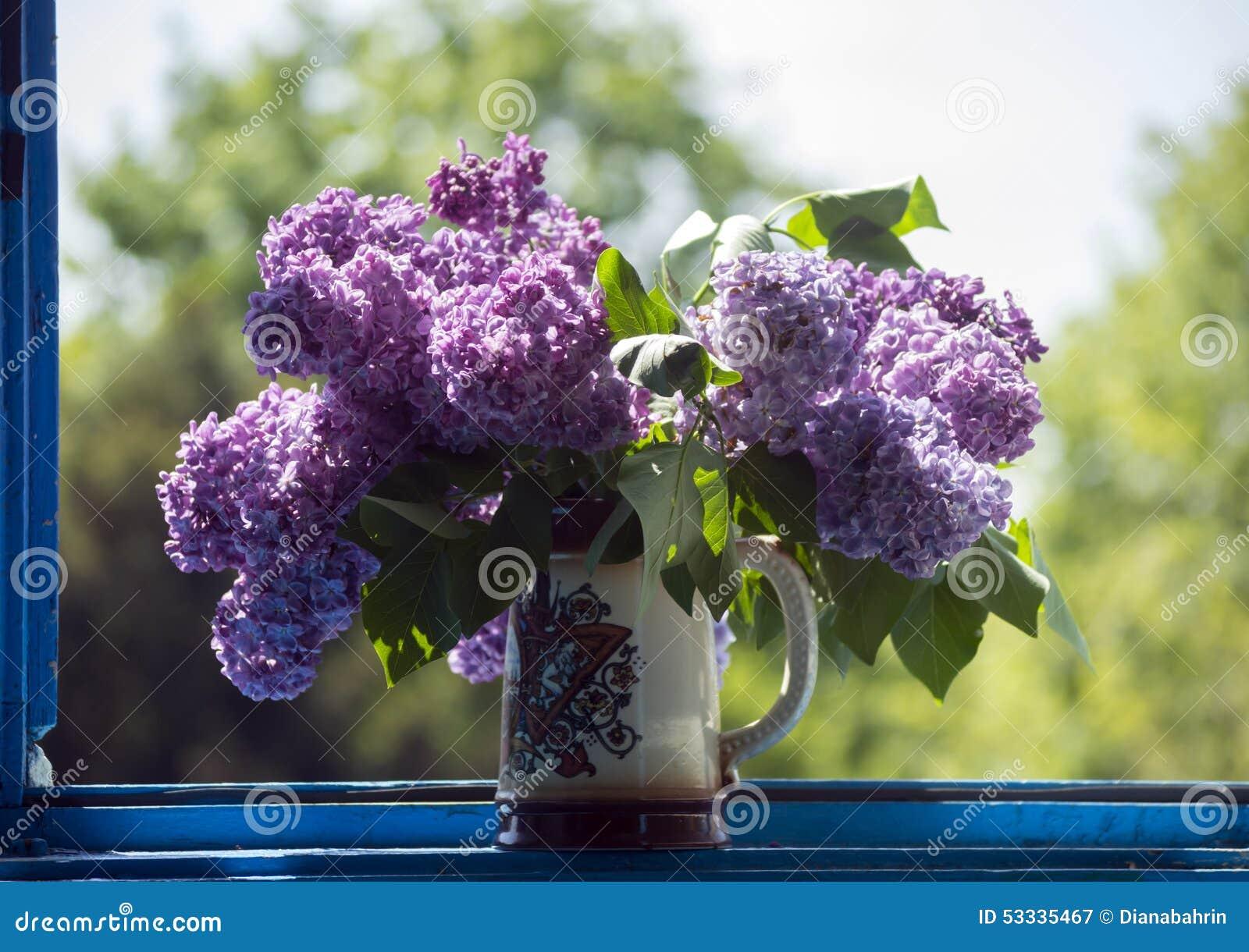 丁香色月天_在一个花瓶的丁香在反对五颜六色的背景的窗口.