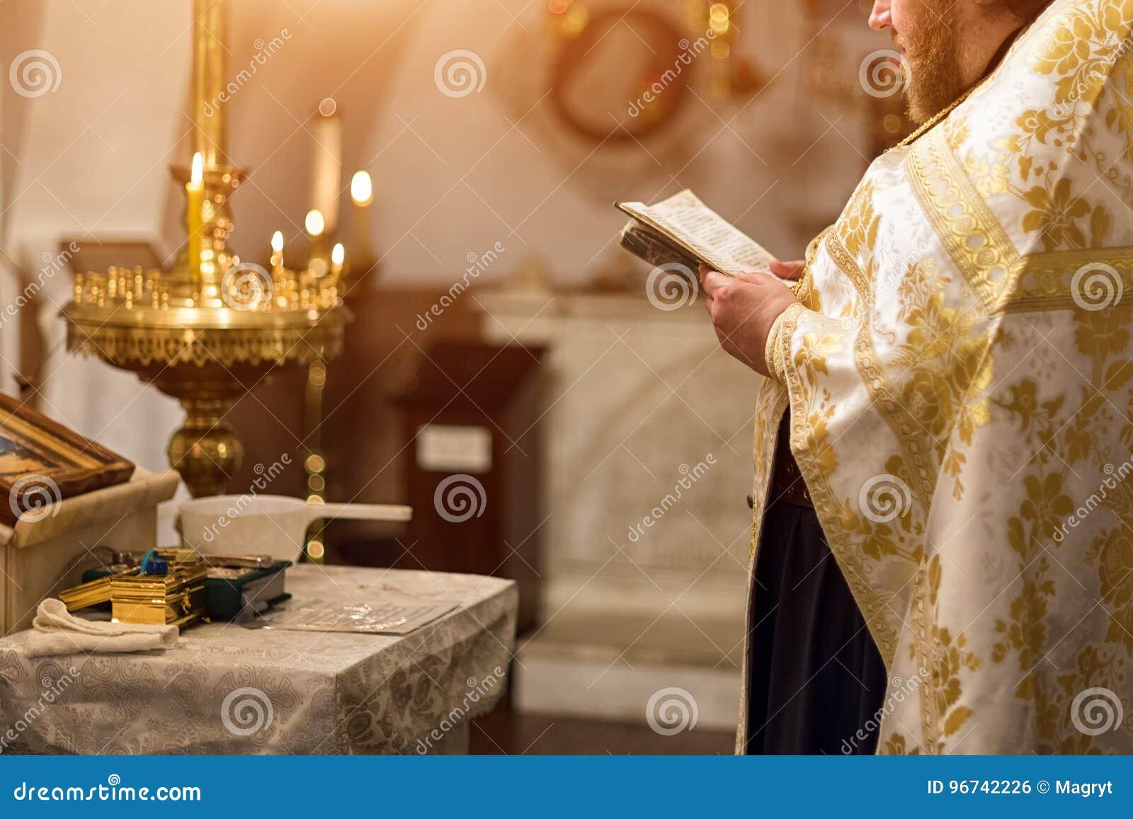 在仪式在基督徒大教堂教会里,圣洁圣礼的事件的教士佩带的金长袍