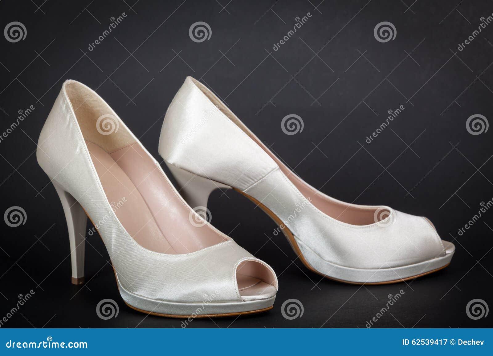 在黑暗的背景的典雅的白色女性鞋子