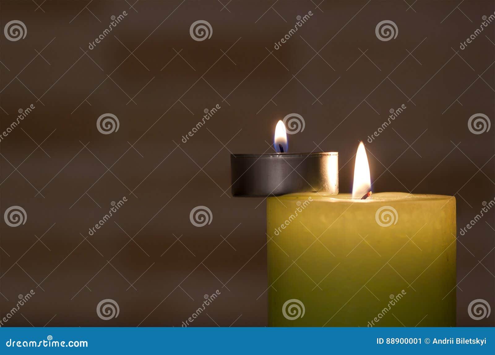 在黑暗的背景的大和小的蜡烛