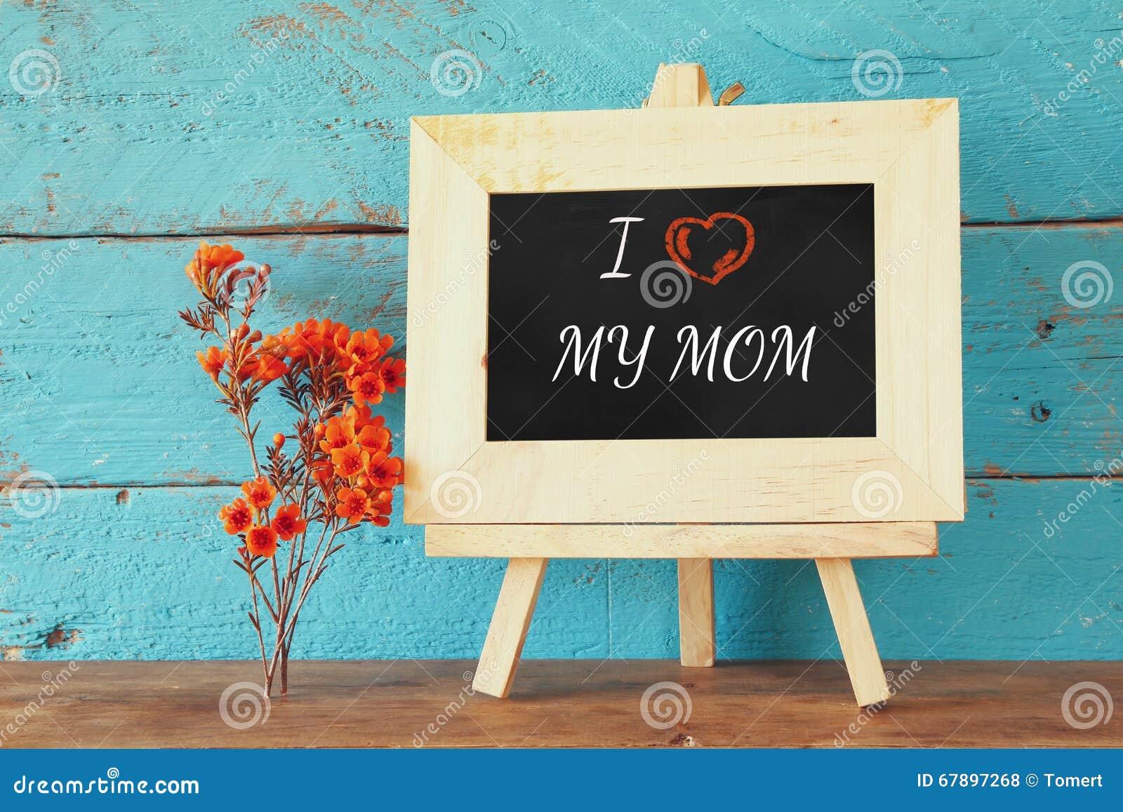 在黑板旁边的花有词组的:我爱我的妈妈,在木桌上 愉快的母亲节概念