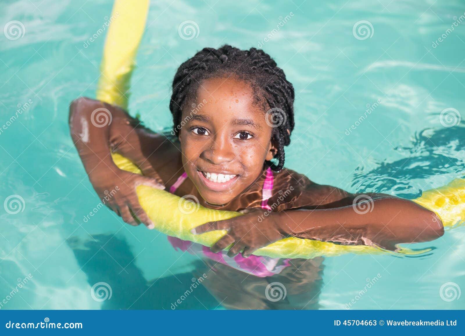 在水池的逗人喜爱的小女孩游泳