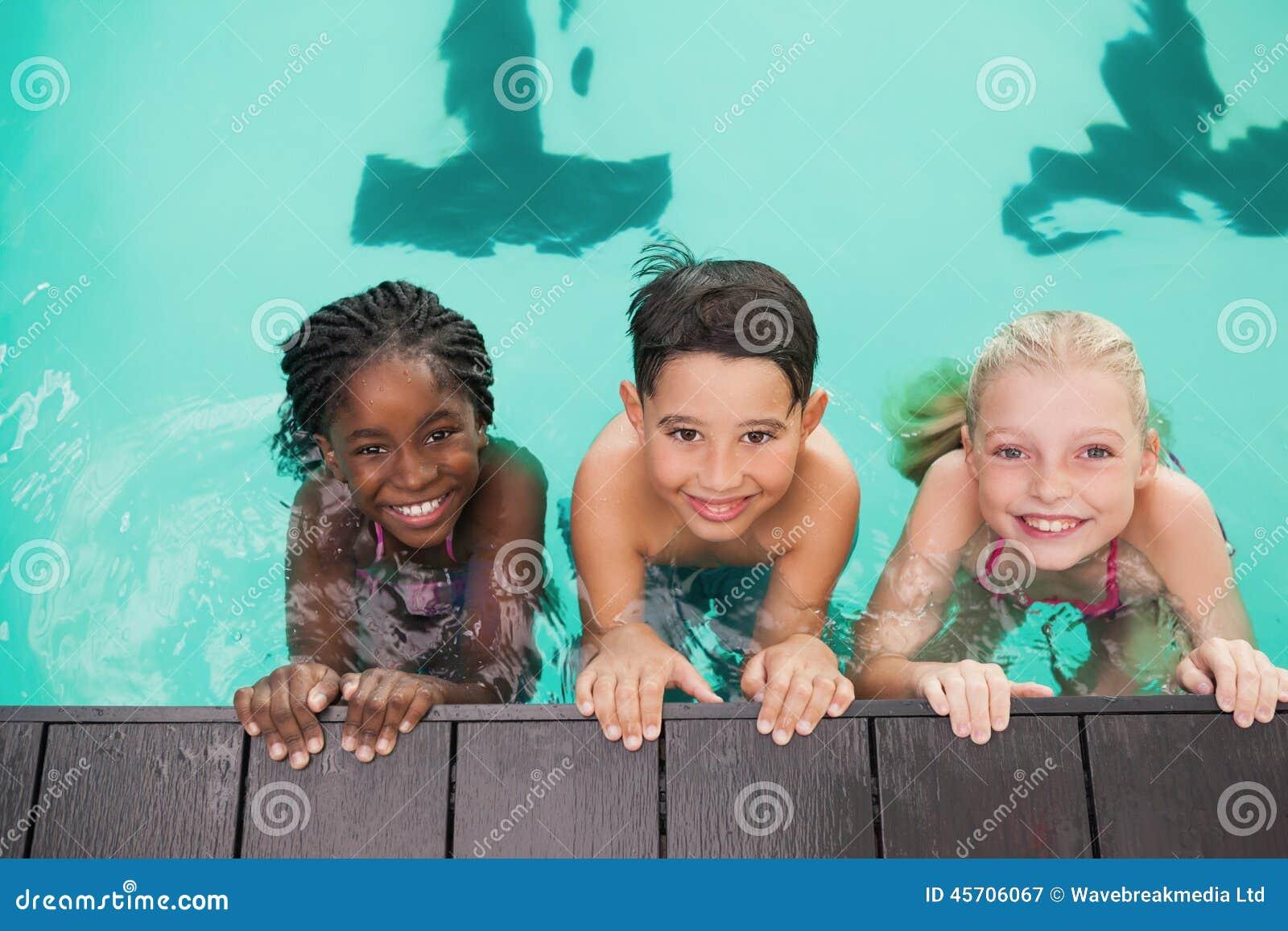 在水池的逗人喜爱的游泳类与教练