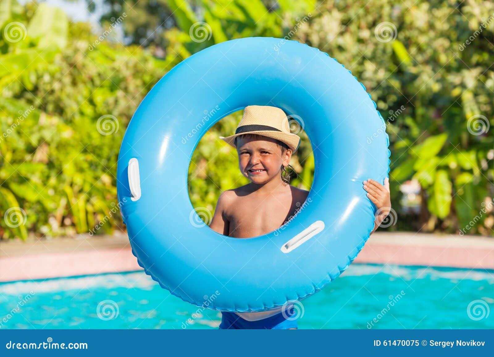 在水池附近拿着可膨胀的圆环的帽子的男孩