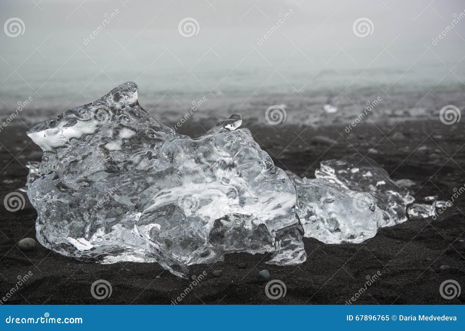 在黑沙子海滩的透明冰川在Jokulsarlon,冰岛