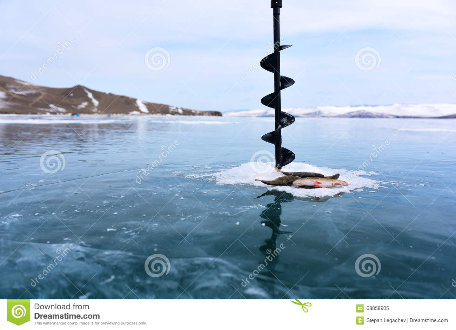 在冻湖冰中间的冬天渔