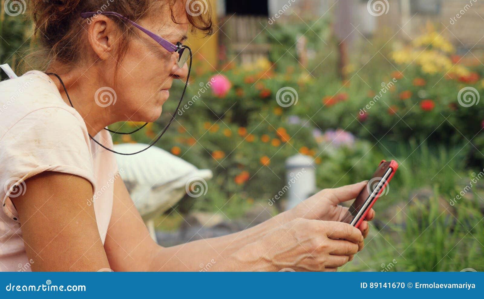 在玻璃变老的严肃的美丽的成熟妇女在庭院里坐摇摆用途一个手机