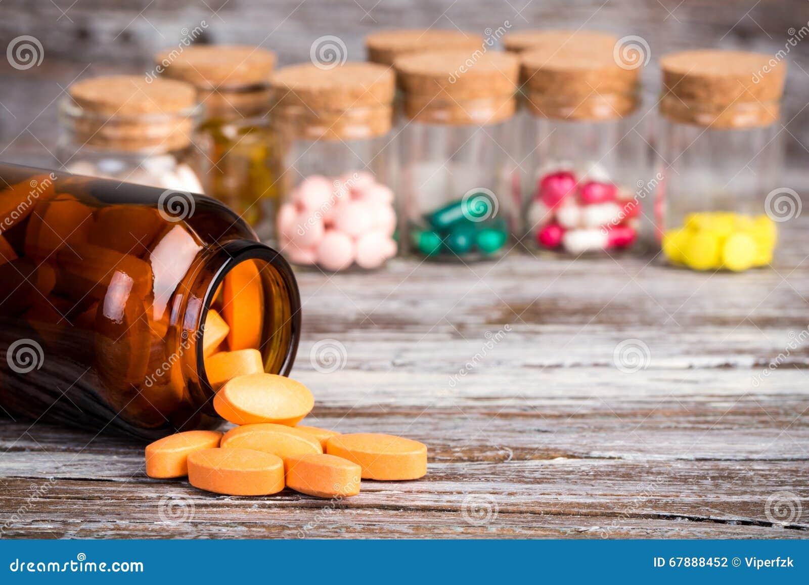 在玻璃容器的橙色药片有其他药片的在背景中