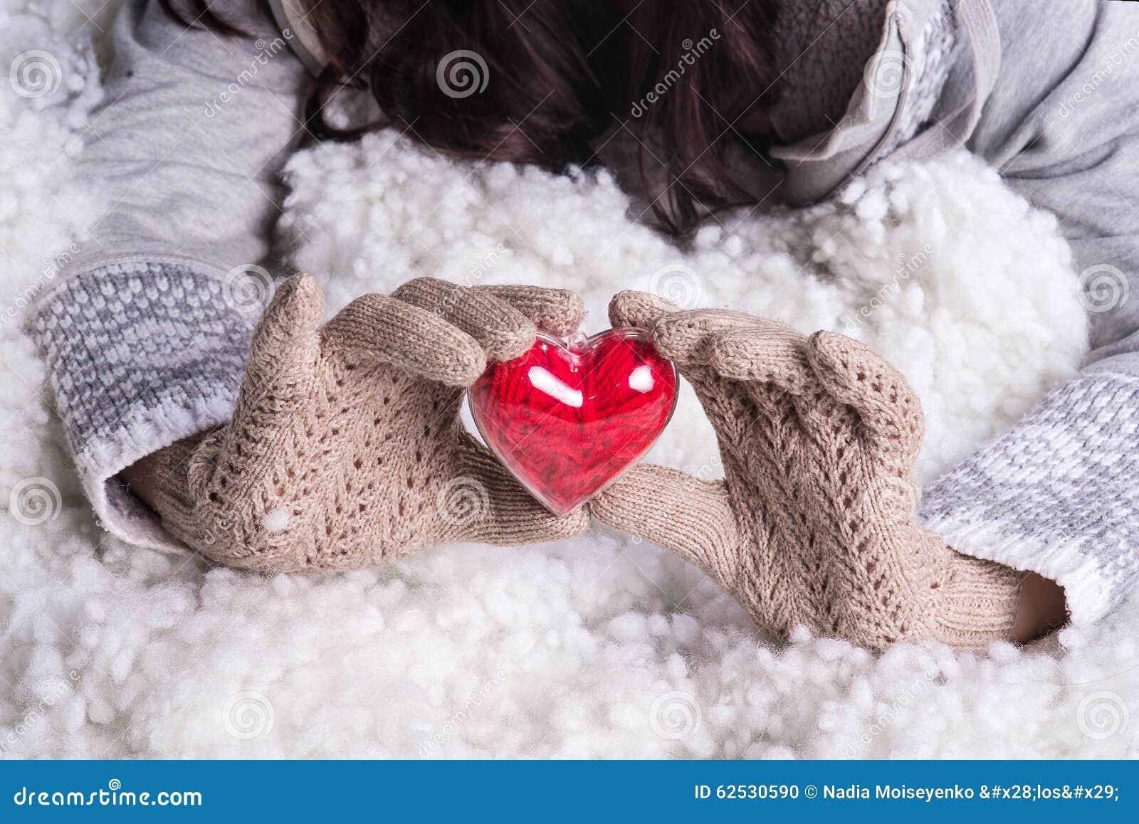 在轻的小野鸭被编织的手套的手拿着在雪的美好的纠缠的葡萄酒红色心脏