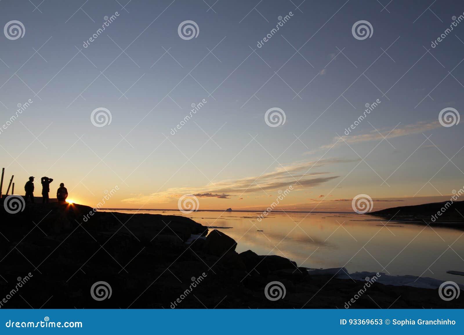 在水的日落与阴影的三个人与云彩whisp
