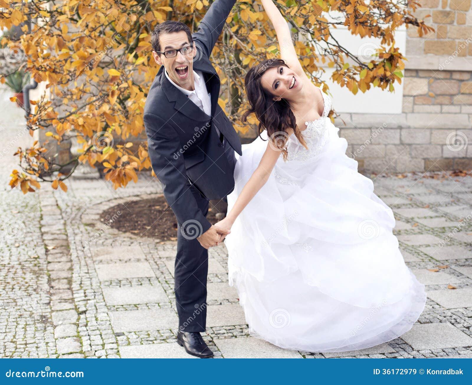 在滑稽的姿势的笑的婚礼夫妇