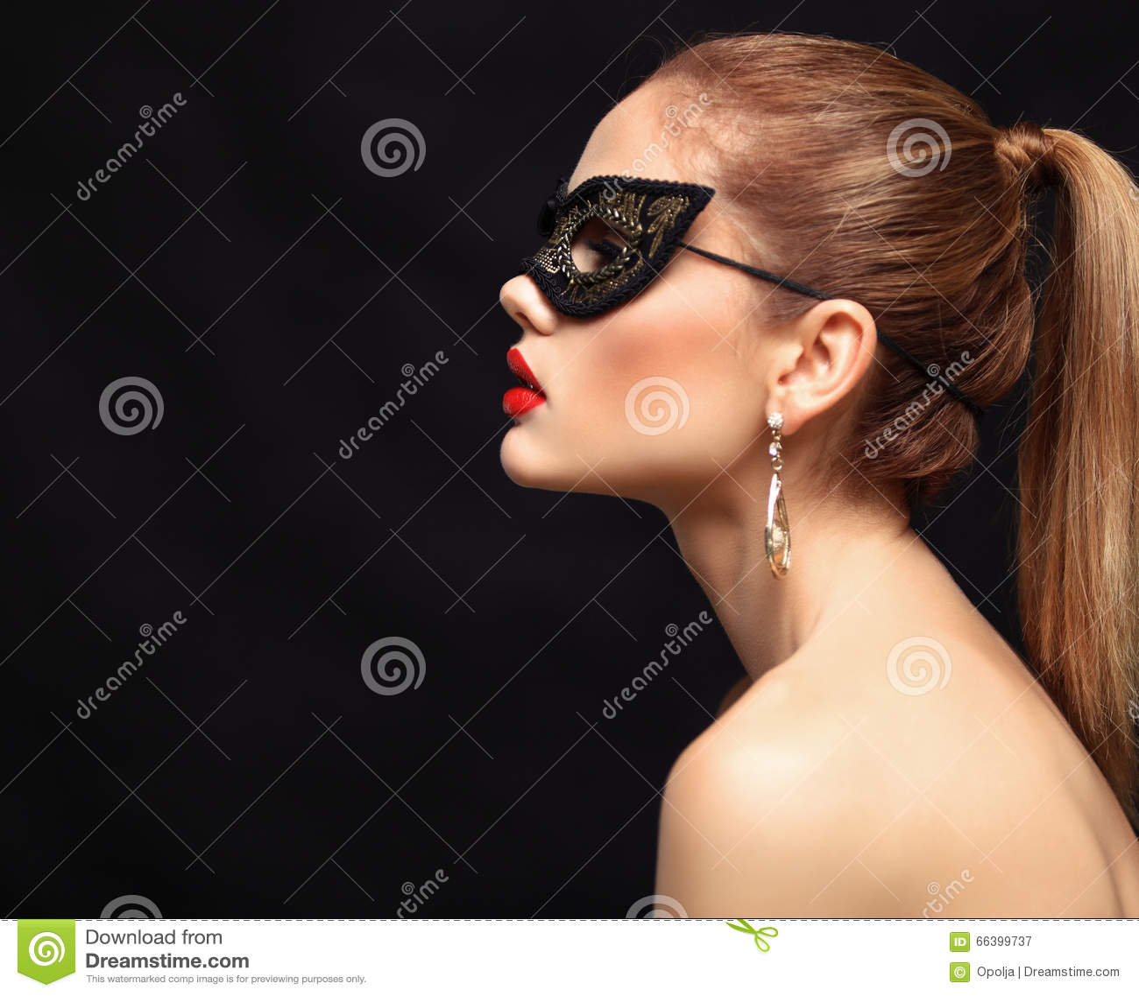 在黑背景隔绝的党的秀丽式样妇女佩带的威尼斯式化妆舞会狂欢节面具 圣诞节和新