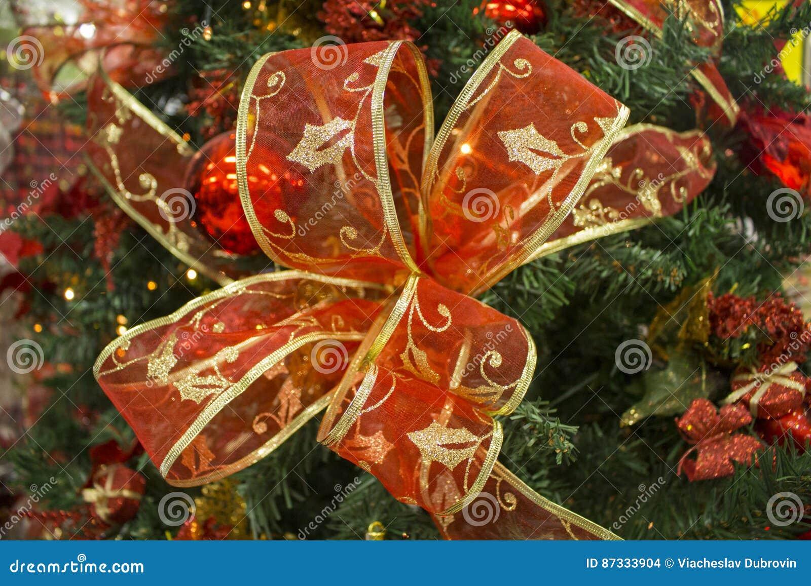 在绿色杉树分支的红色丝带弓 圣诞树装饰品与文本地方的关闭照片