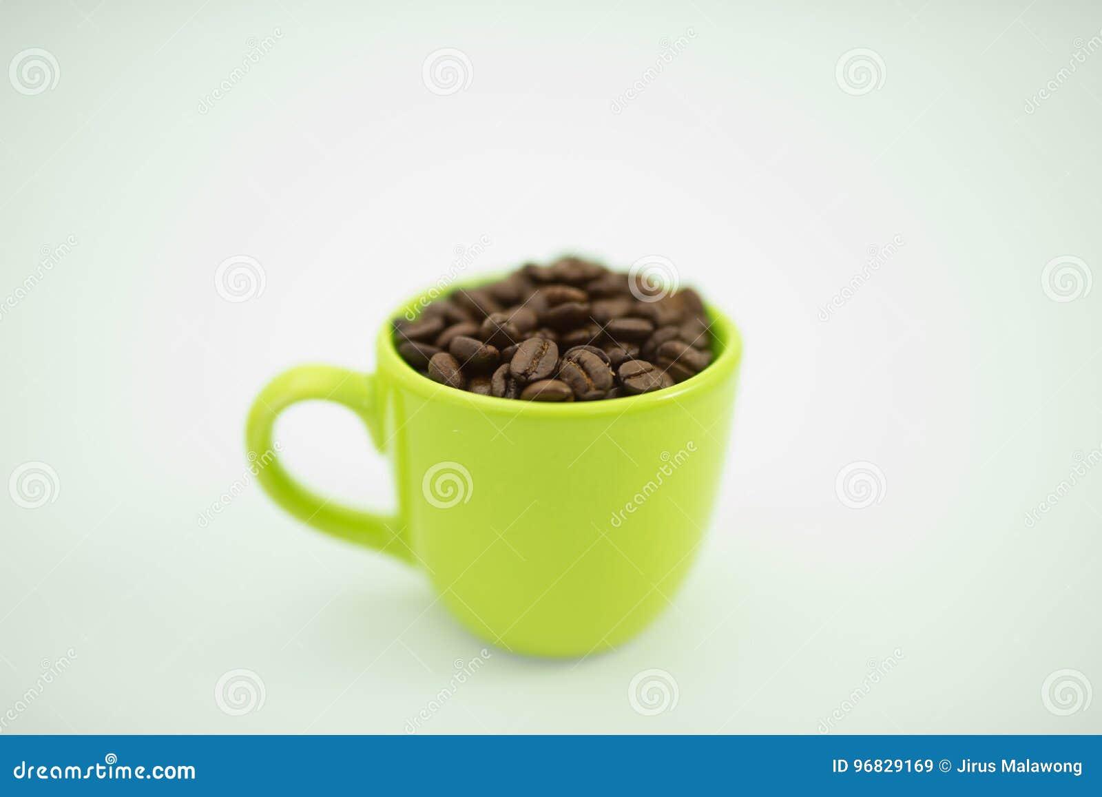 在绿色杯子,白色背景,选择聚焦的咖啡豆