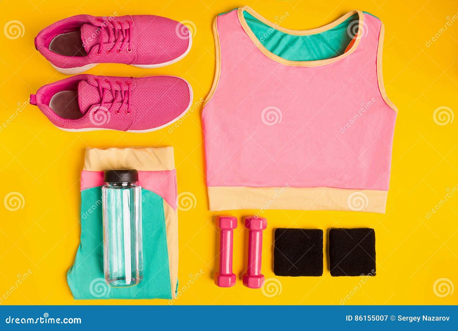 在黄色背景的健身辅助部件 运动鞋、瓶水,哑铃和体育冠上
