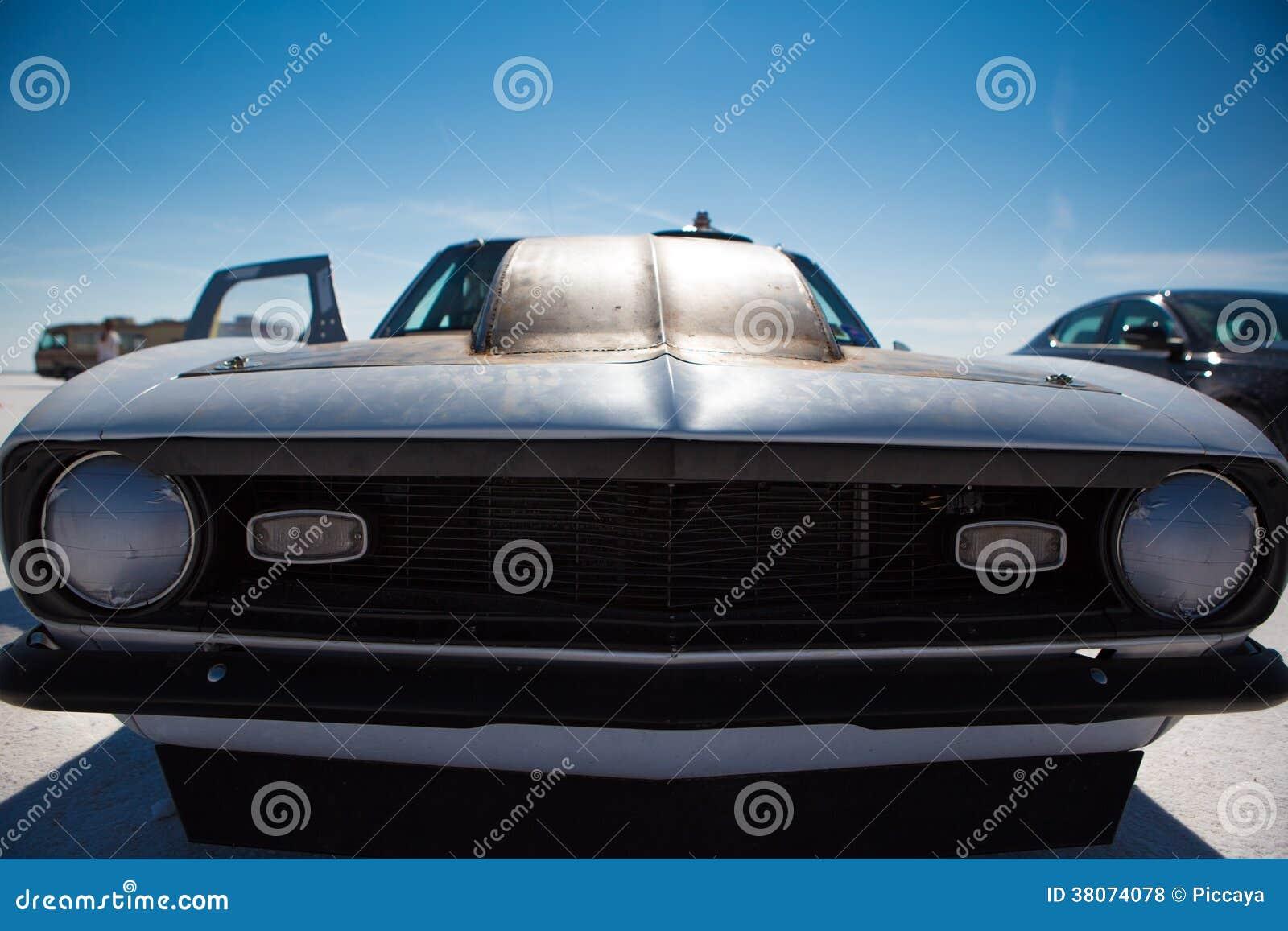 在黑色绘的美国旧车改装的高速马力汽车在速度期间世界