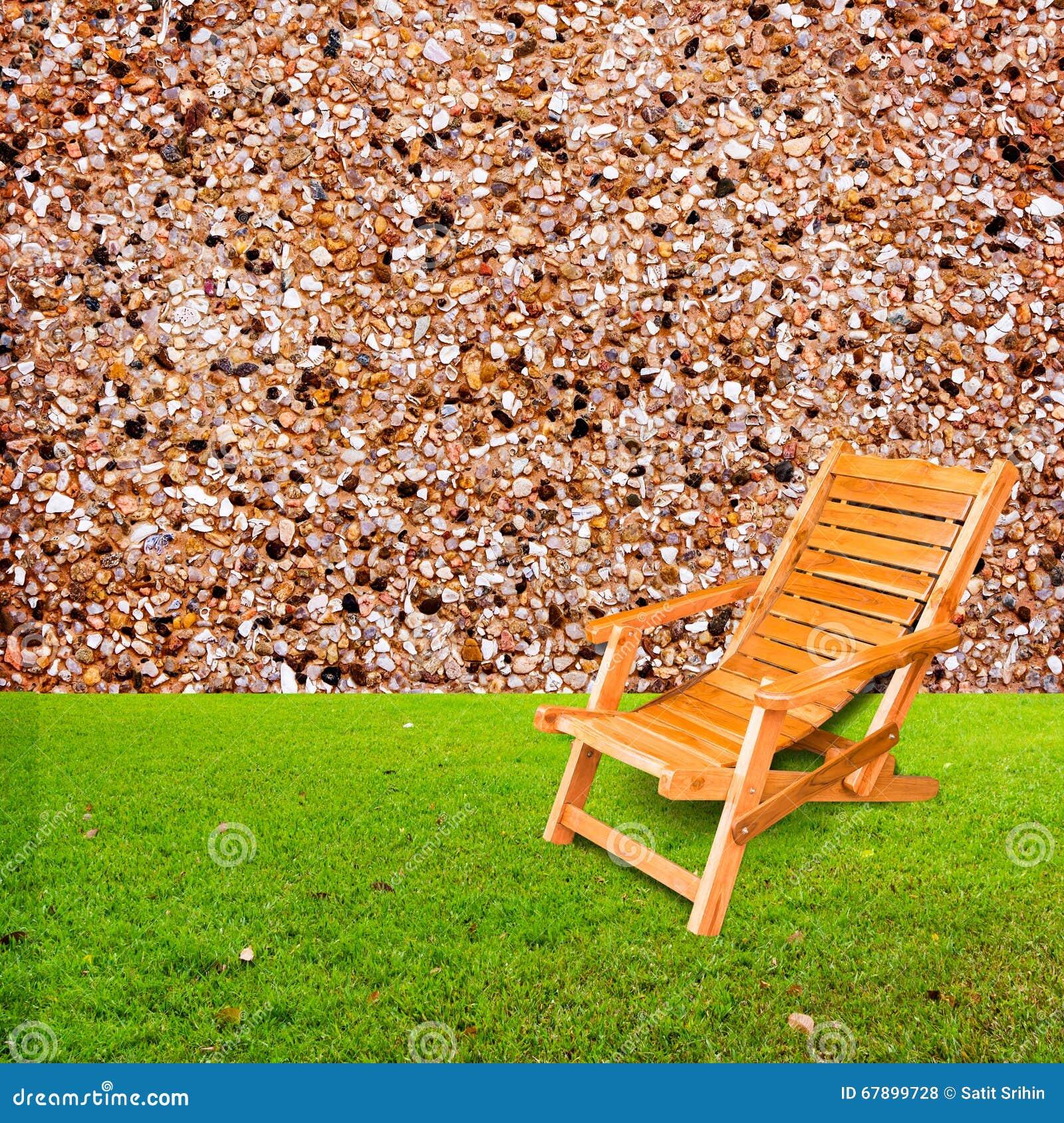 在绿草的木轻便折叠躺椅与石墙