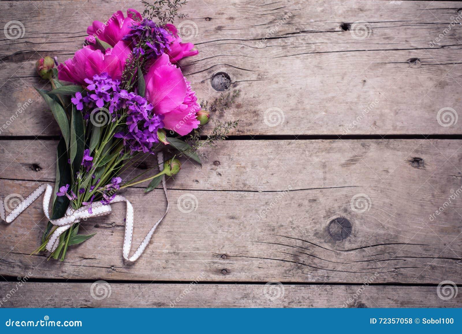 在年迈的木背景的桃红色牡丹花