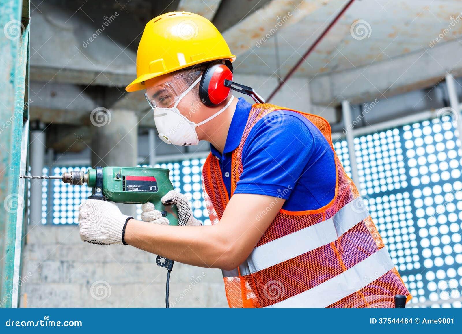 在建造场所墙壁的亚洲工作者钻井