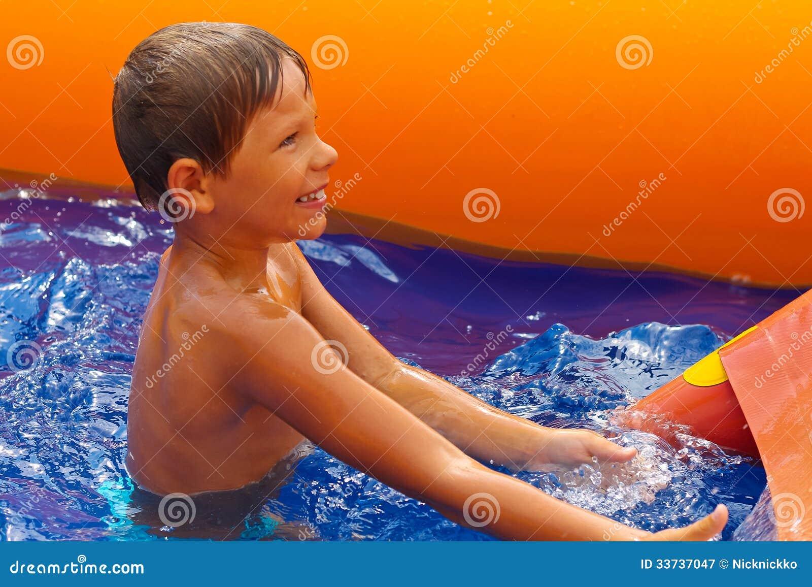 在水滑道附近的微笑的男孩。