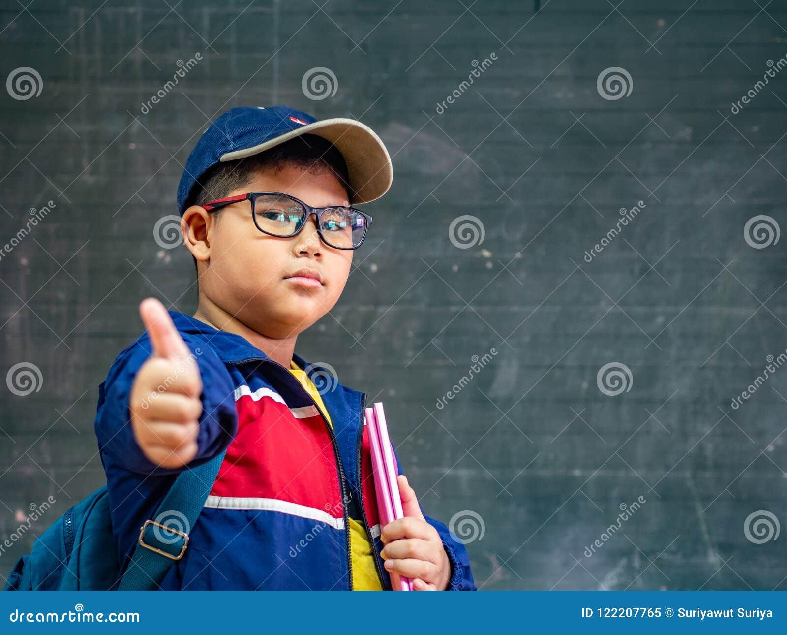 在blackbo前面的愉快的男孩穿戴玻璃微笑和立场
