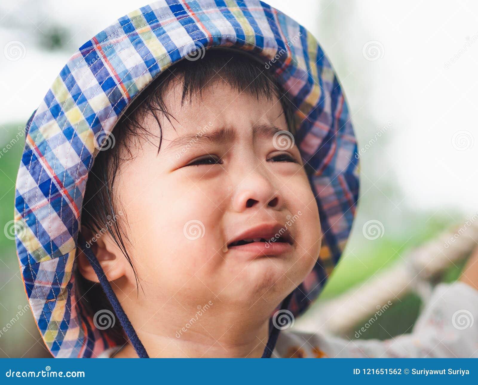 在bokeh背景的哀伤的小女孩哭泣的面孔与葡萄酒fil