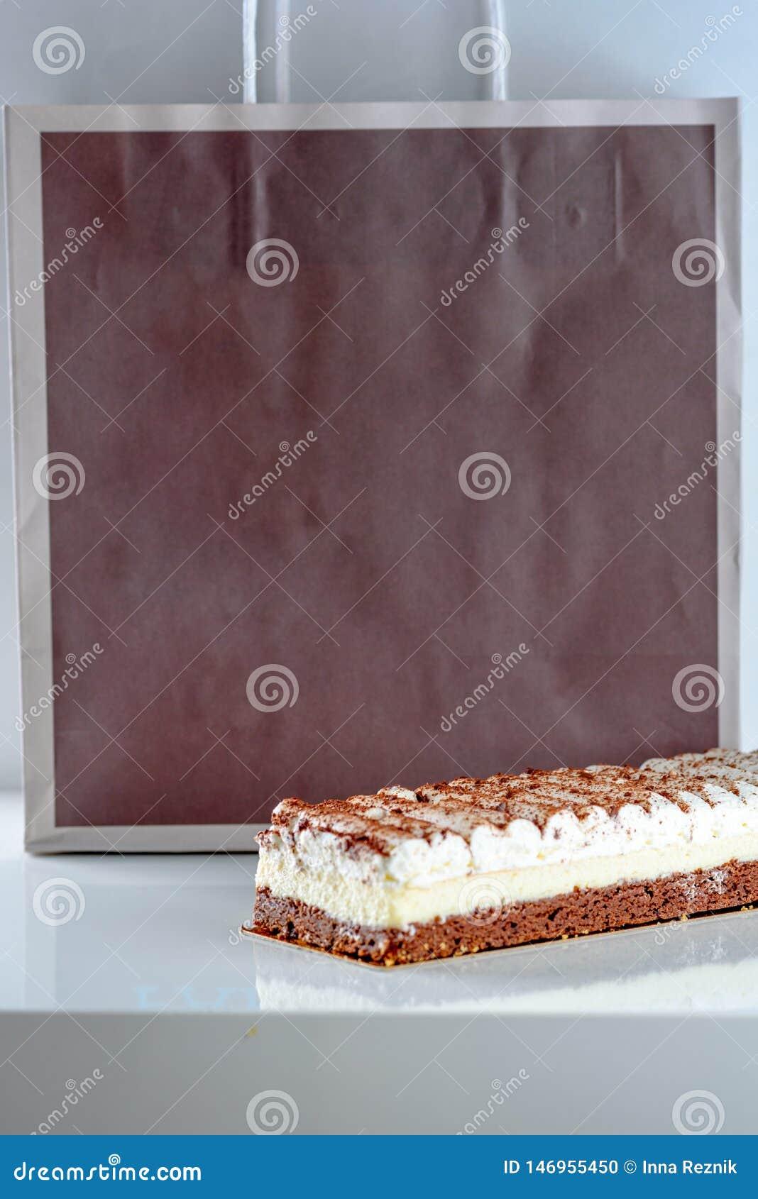 在eco纸袋背景的美丽的可口点心乳酪蛋糕
