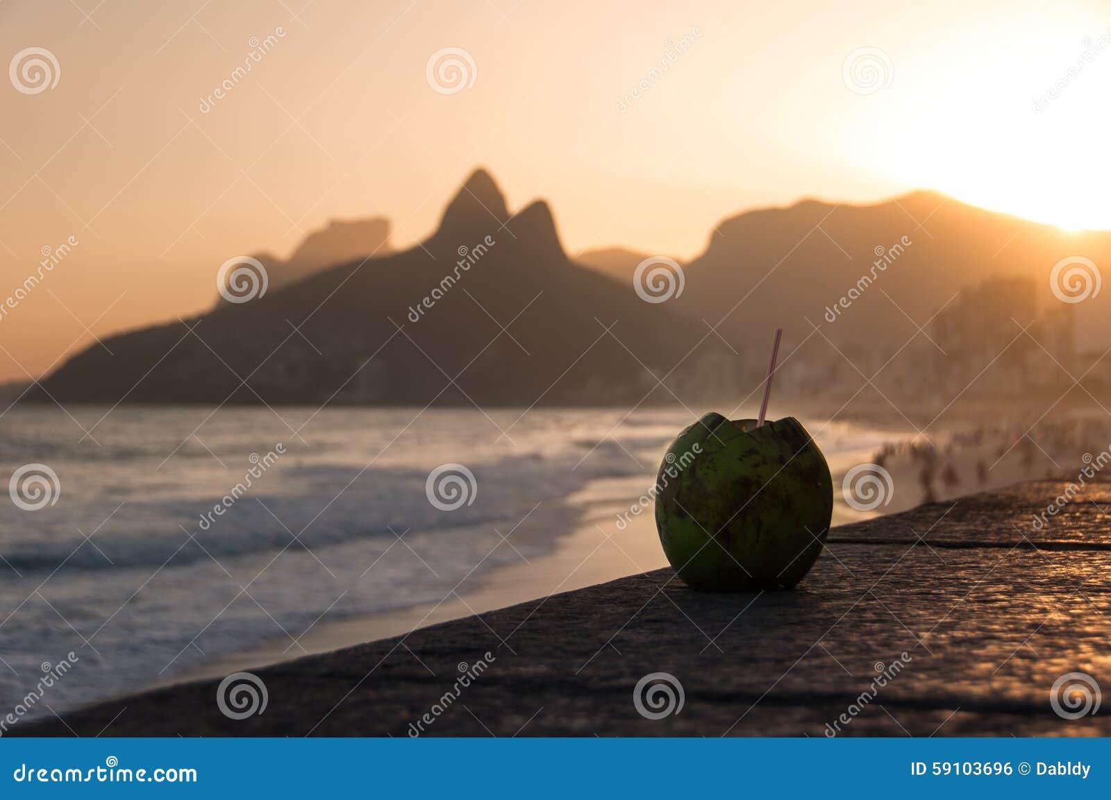 在Ipanema海滩的椰子饮料由日落