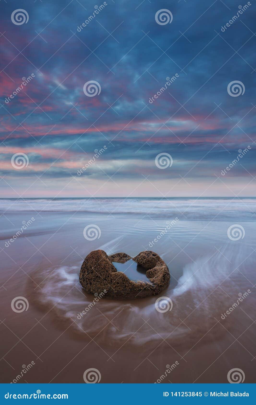 在Koekohe的Moeraki冰砾靠岸,新西兰的东部海岸 日落和长的曝光和剧烈的黎明天空