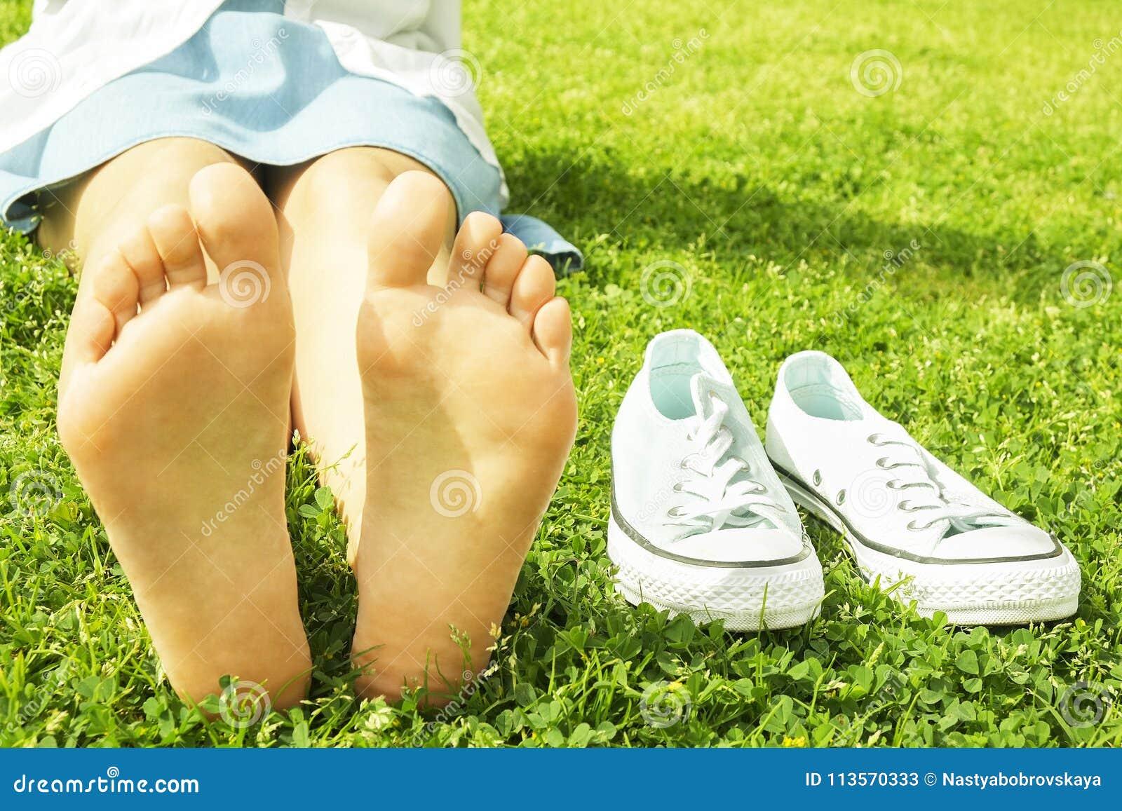 在mawed草坪草的女性赤脚 赤足休息的少妇户外,采取断裂概念 学院校园围场的学生