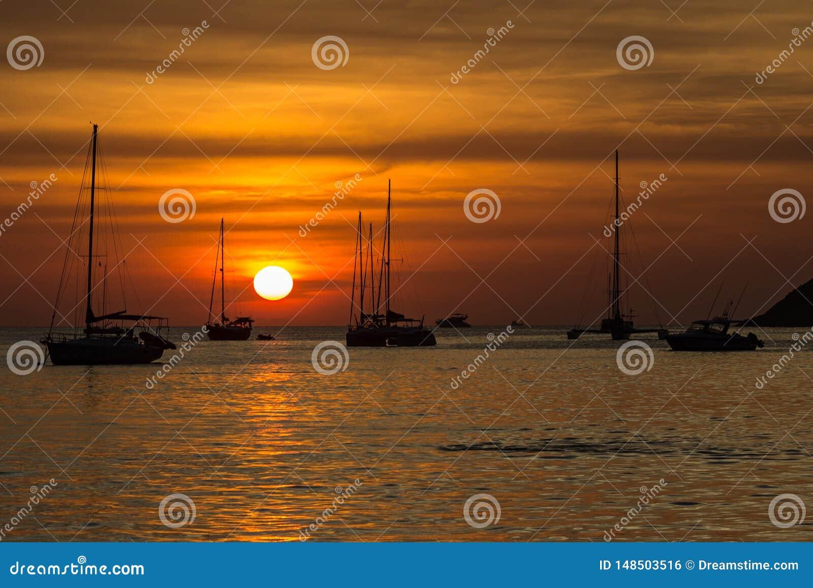 在Nai哈恩海滩的令人惊讶的红色日落在普吉岛