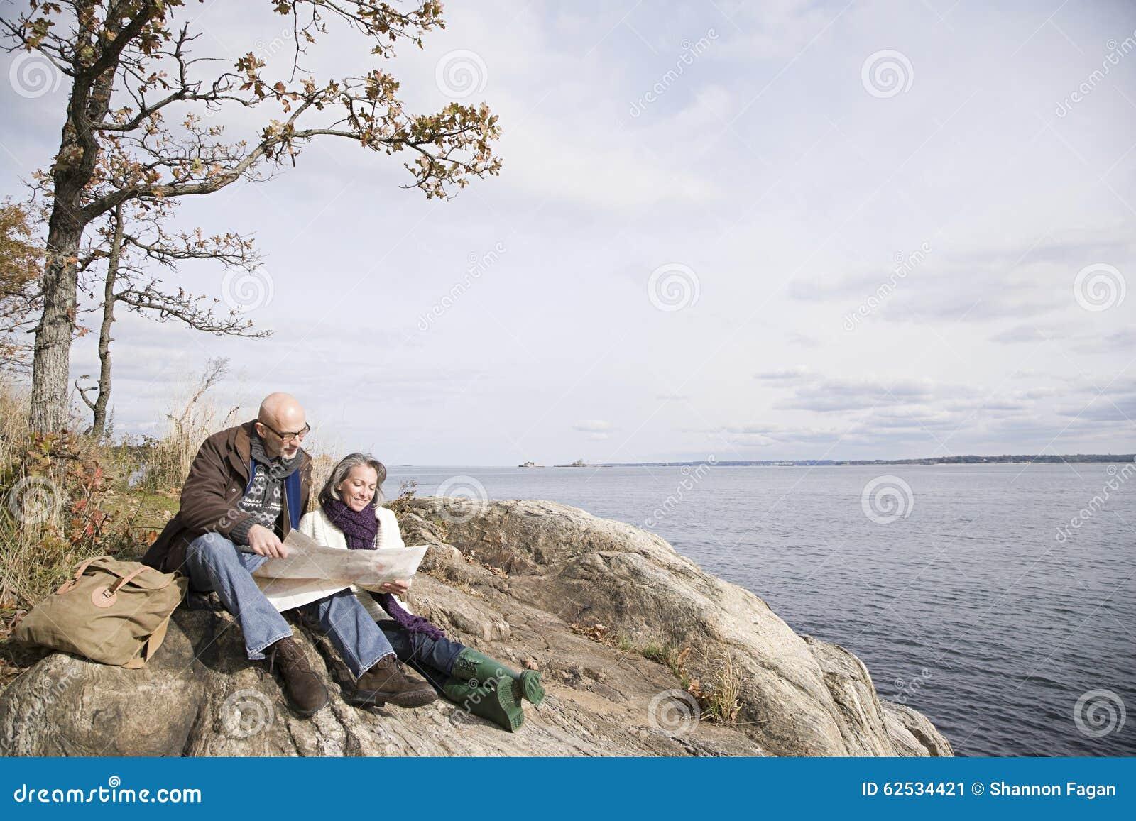 读地图的成熟夫妇在湖附近
