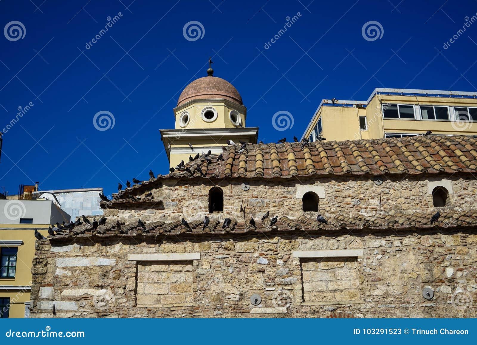 地球口气自然石头的老经典小的教会与在赤土陶器瓦的鸽子有清楚的蓝天和现代大厦的